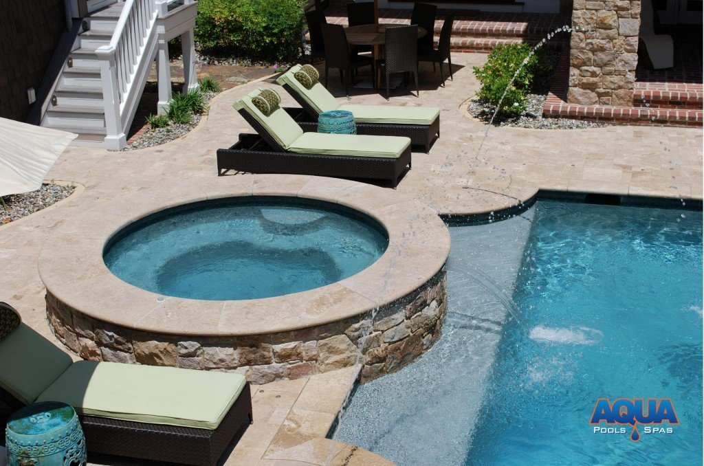 "Instead of having a ""spill over"" into the pool which would dictate the bodies of water (& heat) be shared, we recommend separating the bodies of water.   A waterfall of recirculated pool water can be added to the face of the hot tub to achieve the spillover effect without sharing the water."
